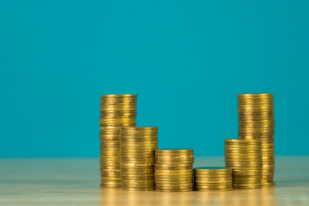 Increasing columns of coins, step of coins stacks on wooden table with copy space for business and financial concept.