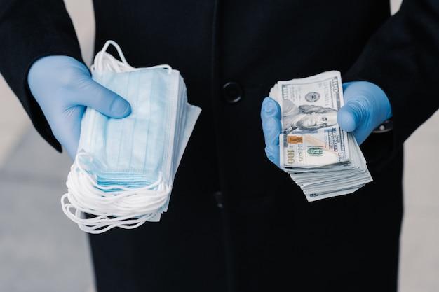 의료 마스크 가격 상승으로 코로나 바이러스 전염병 확산 방지 보호용 의료 장갑을 착용 한 사람은 마스크와 많은 돈을 쌓아 둔다. 수익성있는 사업, 격리 중 추측.