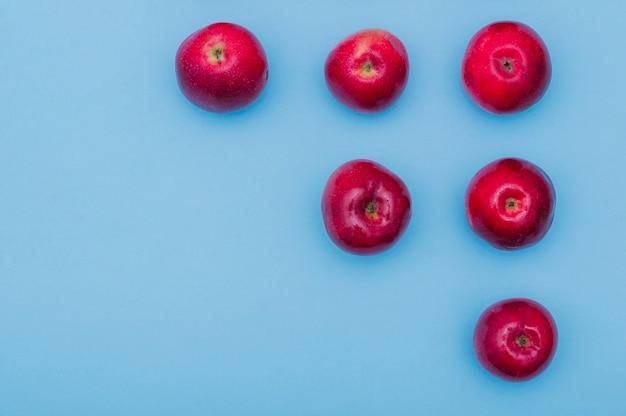 Увеличение ряда красных свежих яблок на синем фоне