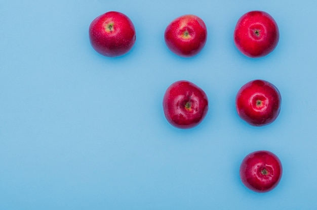 Increasing row of red fresh apples on blue background