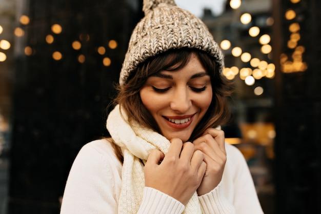 Incredibile signora affascinante con cappello bianco lavorato a maglia e maglione lavorato a maglia sorridente