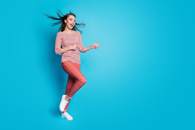 Невероятные скидки на рекламу. полноразмерная фотография жизнерадостной девушки-промоутера указывает на то, что указательный палец coyspace носит белые брюки, обувь на синем фоне.