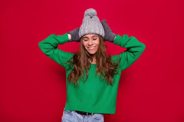 緑のプルオーバーと灰色の冬のキャップを身に着けている信じられないほどの女の子は、紙吹雪と赤い背景の上で楽しんでいます。新年のプレゼント、誕生日を祝う、前向きな感情を表現する