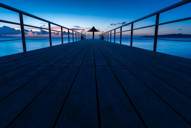 パステル ブルー トーンの桟橋の信じられないほど長い露出。パラソルにつながる木の板。