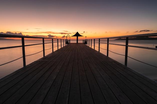 オレンジ、イエロー、ピンクのパステル カラーの桟橋の信じられないほどの長時間露光。パラソルにつながる木の板。
