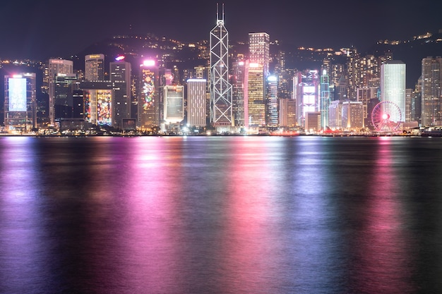 The incredible night cityscape view of lights on the water on victoria harbour in hong kong