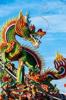 Incredible statue of super colorful dragon seated looking back with long ears and mustaches