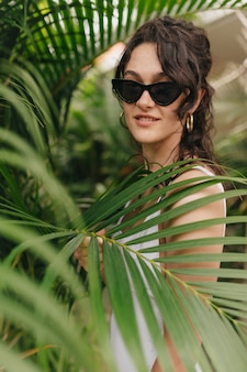Incredible stylish pretty woman in sunglasses with beautiful earnings posing  through exotic trees