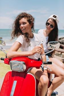 信じられないほどの2人の幸せな女性は、海と自然、真の幸せな感情、旅行、旅行、幸せな感情のそばの島で、太陽の下で赤いバイクで楽しんで旅行しています