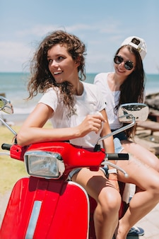Incredible two happy woman have fun and traveling by red motorbike in sunshine on the island by the ocean and nature, true happy emotions, travel, trip, happy emotions
