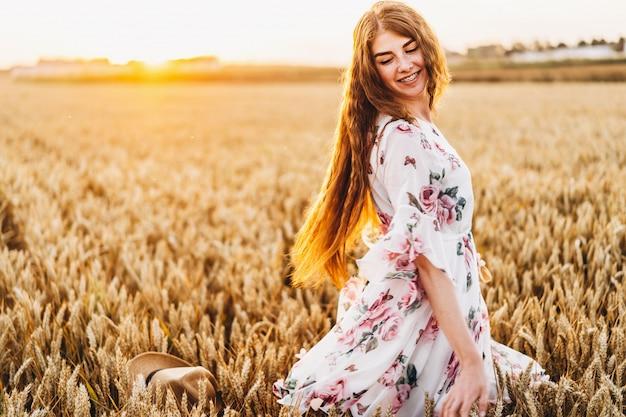 長い巻き毛とそばかすの顔を持つ信じられないほどの若い女性。日没時の麦畑でポーズをとってドレスを着た女性。ポートレートを閉じる
