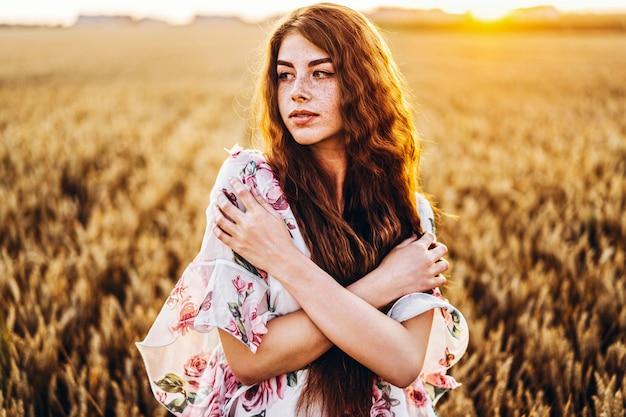 長い巻き毛とそばかすのある顔を持つ信じられないほどの若い女性。夕暮れ時の麦畑でポーズをとってドレスを着た女性。ポートレートを閉じる