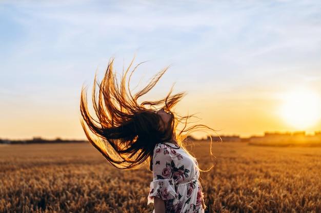 長い巻き毛を持つ信じられないほどの若い女性。日没で麦畑でポーズをとってドレスを着た女性と髪を傾ける頭を真っすぐ