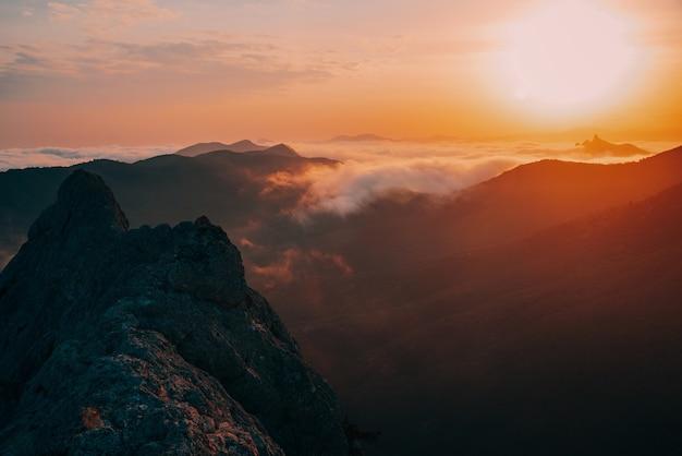 霧の中の山々の信じられないほど素晴らしい美しい黄金の夕日