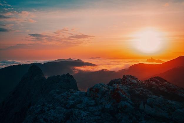 霧の中の山々の信じられないほど素晴らしい美しい黄金の夕日。
