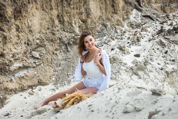 日光浴と夏の自由な時間を楽しんで白い砂の上に横たわって信じられないほどかわいい若い女の子