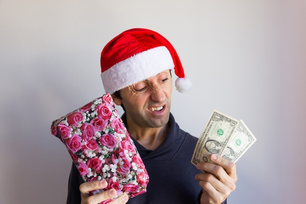 Incredulous young man with santa hat holding wrapped gift and little cash with skeptical look