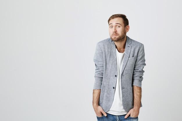Нерешительный и невежественный скромный бородатый парень с руками в карманах