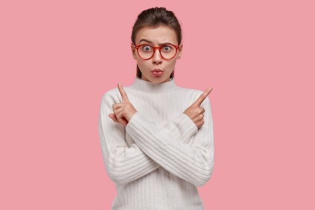 Нерешительная злая женщина показывает в разные стороны, удивлена отрицательным выражением лица, носит белый свитер