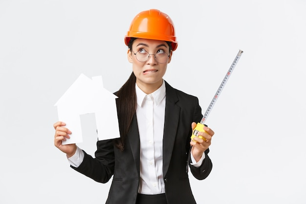 Indecisive asian female architect, construction engineer in helmet and business suit holding house maket and tape measure, biting lip unsure, looking away thoughtful, searching solution