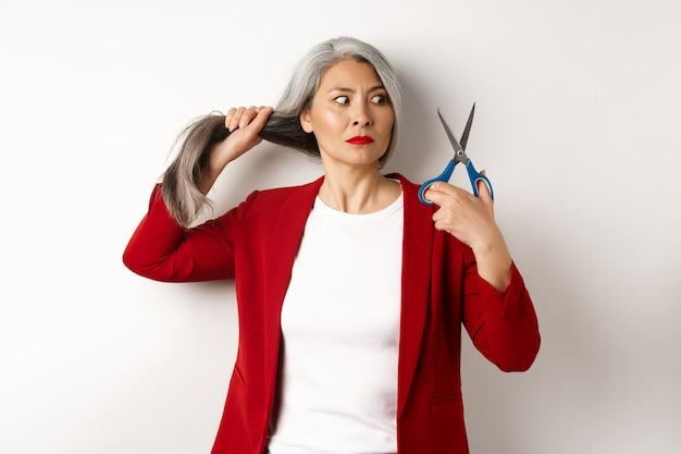 Нерешительная азиатская женщина, держащая ножницы и сомневающаяся, думающая о том, чтобы подстричь волосы, меняющая стрижка, стоя на белом фоне
