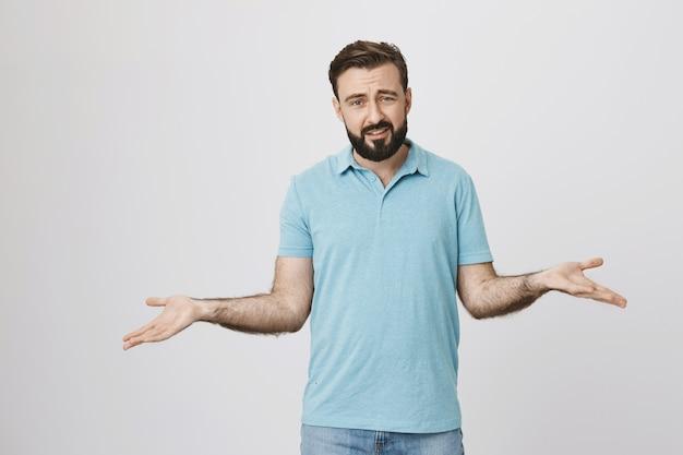 Нерешительный бородатый парень пожимает плечами, не знаю, чувствуя себя невежественным