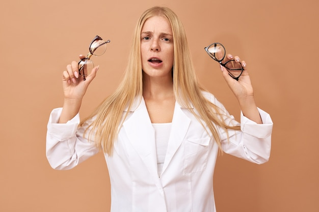 의심스러운 표정을 가진 안경을 들고 우유부단 한 아름다운 젊은 여성 고객