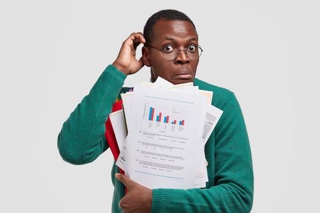 L'uomo nero indeciso si gratta la testa, trasporta documenti con dati e diagramma