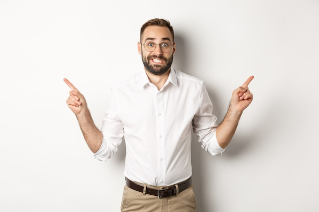 Indecisive businessman pointing sideways, showing two variants, struggling make choice, standing over white background.