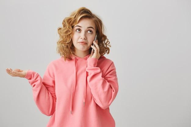 Нерешительная бестолковая девушка разговаривает по телефону, недоуменно пожимая плечами