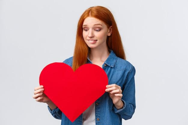 Нерешительная милая и робкая, стеснительная рыжая женщина хочет признаться в любви, показать сочувствие, неуверенная, дарить подарок на день святого валентина или нет, держит большое красное сердце, кусает губы, беспокоится