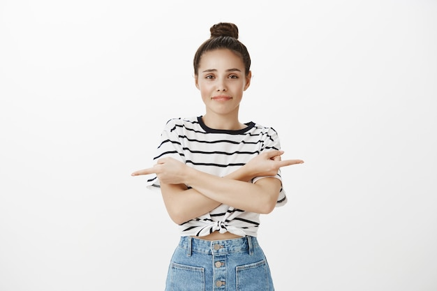 Indecisive cute girl need help with choice, pointing fingers sideways, don't know what to pick