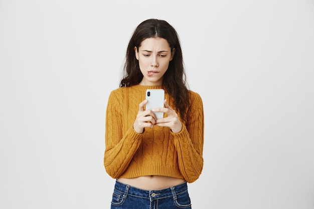 Indecisive girl receive frustrating message, looking hesitant at mobile phone