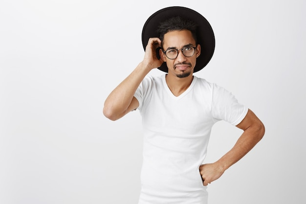 Indecisive handsome african-american man in glasses and hat scratch head puzzled, looking confused