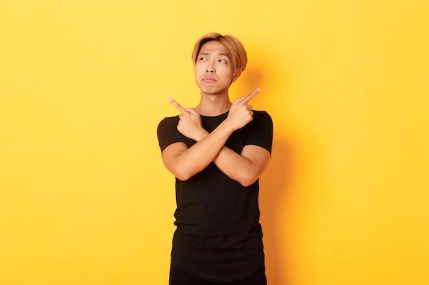 Нерешительный красивый азиатский парень выглядит смущенным, показывает пальцами в сторону, стоит у желтой стены