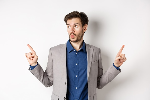 Indecisive male entrepreneur in suit pointing fingers sideways, choosing between two variants, looking at left logo pensive, standing on white background.