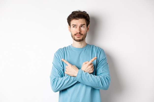 Indecisive man making choice, pointing fingers sideways at two variants and deciding, looking pensive at left side, standing on white background.