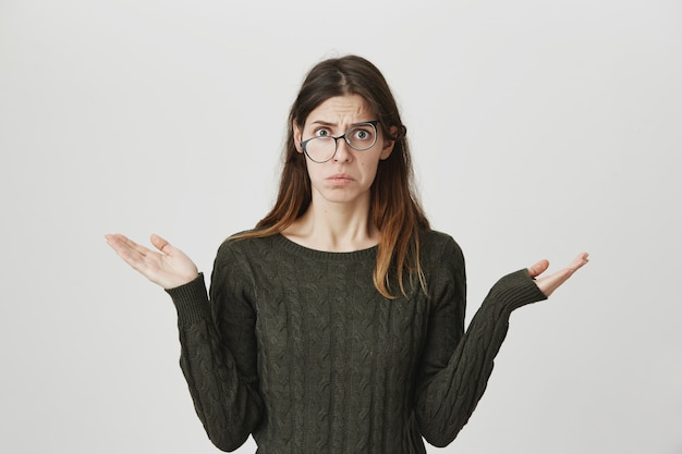 Indecisive perplexed young woman shrugging, don't know, have no idea