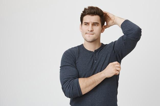 Нерешительный озадаченный красивый спортсмен-мужчина почесывает голову, думая