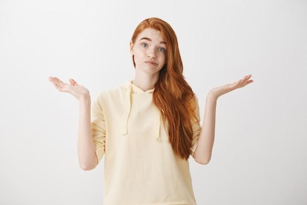 手で肩をすくめて優柔不断な赤毛の女の子が横に広がり、何も知らない