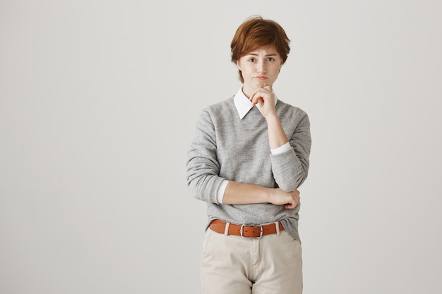 Indecisive redhead girl with short haircut posing against the white wall
