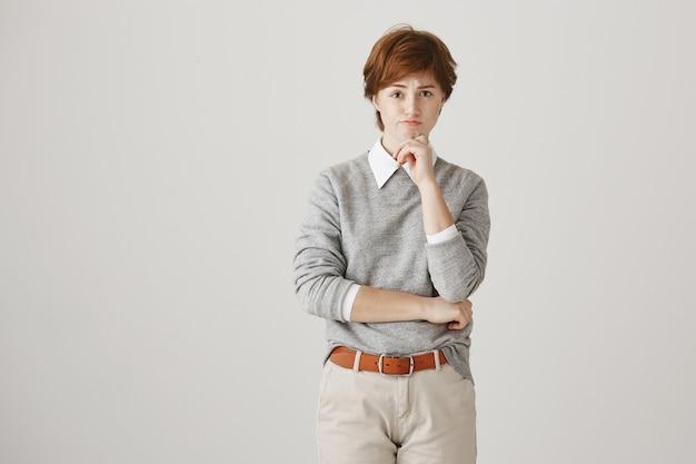 Ragazza rossa indecisa con taglio di capelli corto in posa contro il muro bianco