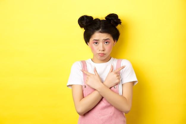 優柔不断な臆病なアジアの女の子が横向きで、左右の道を示し、動揺し、黄色に悲しんで立っています。
