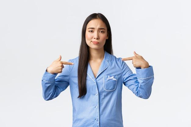 La ragazza asiatica indecisa e insicura in pigiama blu sorride incerta e indica se stessa, non essendo sicura delle proprie capacità, parlando di se stessa, in piedi su sfondo bianco