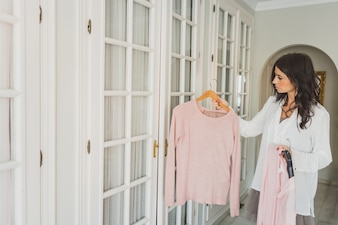 Indecisive woman checking a pink jersey