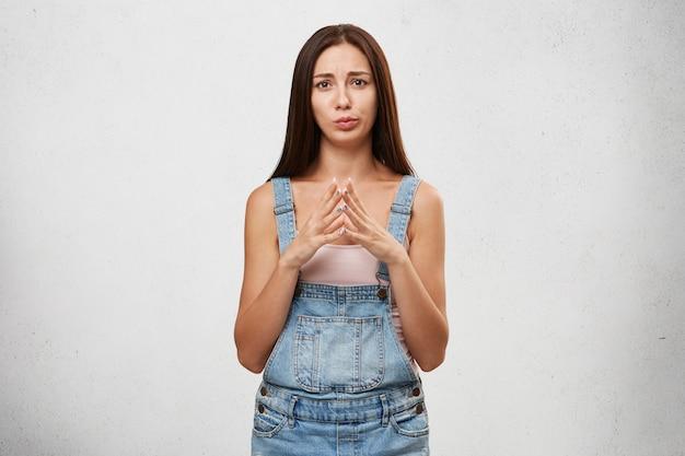 重要な決定をすることを躊躇している優柔不断な女性。魅力的な若いブルネットの女性の手を握り締めて、彼女の表情は焦りと心配を表現しています。人間の感情、感情、反応