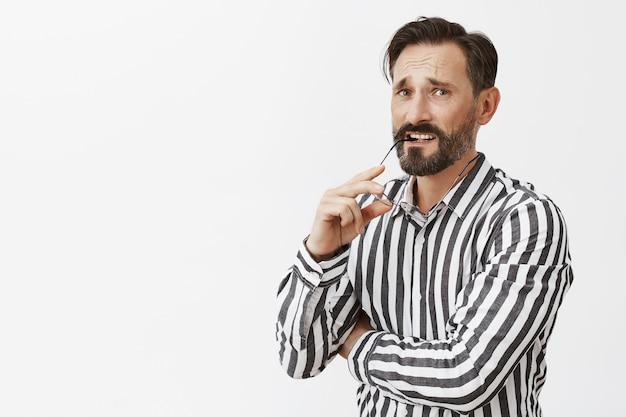 Uomo maturo barbuto preoccupato indeciso in posa