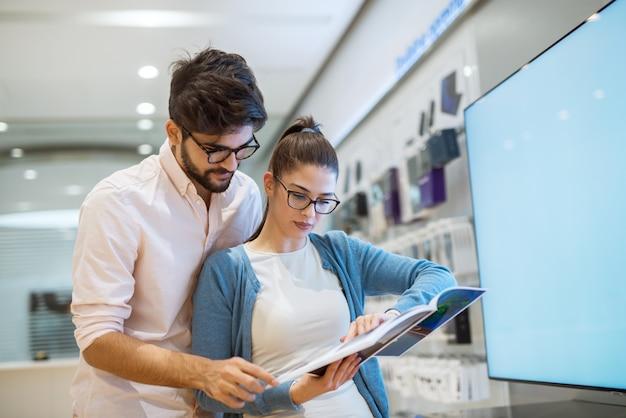 Нерешительная молодая привлекательная пара, делающая покупки в электронном магазине, изучающем каталог товаров.