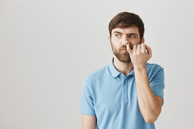 Indecisive young bearded man posing