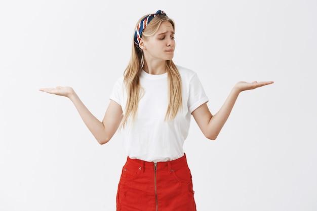 白い壁に向かってポーズをとる優柔不断な若いブロンドの女の子